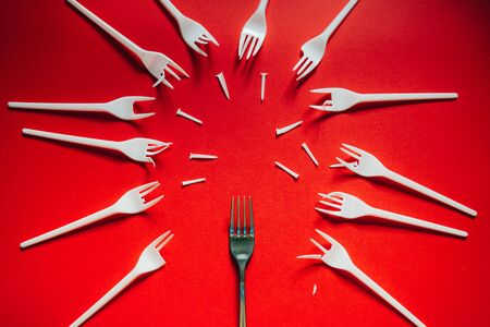 A lot of broken plastic forks vs a metal one on red background. The concept of environmental problems, environmental pollution by plastic waste. Flat lay. 版權商用圖片