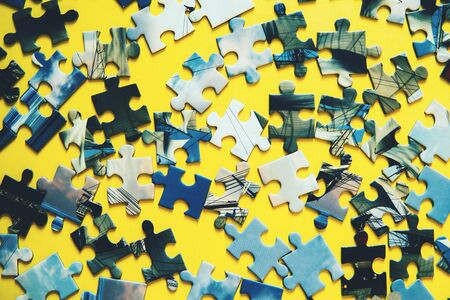 A lot of blue puzzle pieces on a yellow background.
