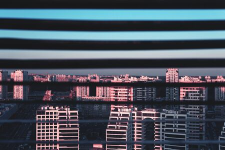Top view of the city at dawn through the blinds. The concept of the city as a prison. Trendy combination of pink and blue colors.