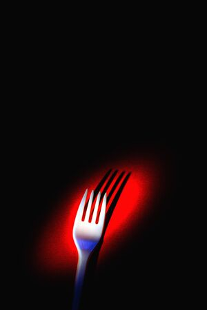 A plastic fork on a red background in dramatic light. The concept of environmental problems, environmental pollution by plastic waste. Top view, vertical. 版權商用圖片