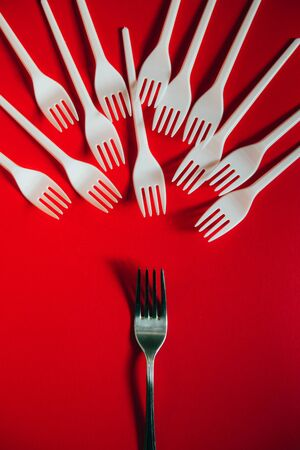 A lot of broken plastic forks vs a metal one on red background. The concept of environmental problems, environmental pollution by plastic waste. Top view, vertical, flat lay. 版權商用圖片