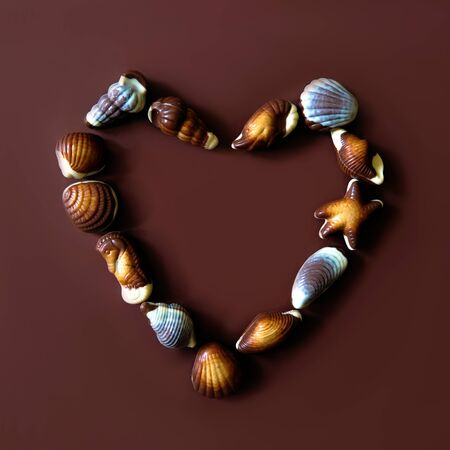 Assorted Chocolate pralines with sea and love concept on brown background. Copy space. Stock Photo - 129923081