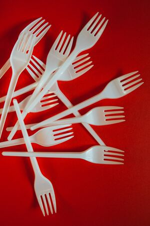 A lot of plastic forks on red background. Concept of environmental problems, environmental pollution by plastic waste. Top view, close up, vertical. 版權商用圖片