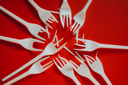 A lot of broken plastic forks on red background. Concept of environmental problems, environmental pollution by plastic waste. Top view, close up. 版權商用圖片
