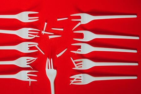 A lot of broken plastic forks on red background. Concept of environmental problems, environmental pollution by plastic waste. Top view, close up. 版權商用圖片 - 129923088