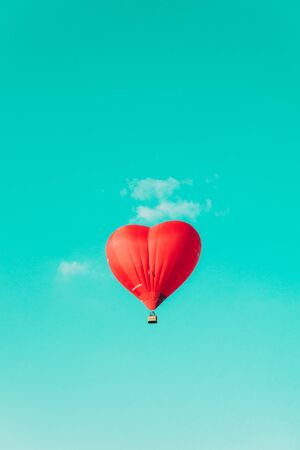 Red balloon in the shape of a heart against the blue sky and some light clouds. Stock fotó