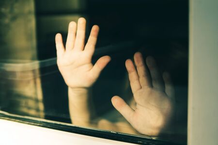 Child standing with outstretched hands behind glass. Violence and fear concept. 版權商用圖片