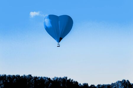 Blue hot air balloon in the shape of a heart against the sky and some light clouds. Love concept. Stock fotó