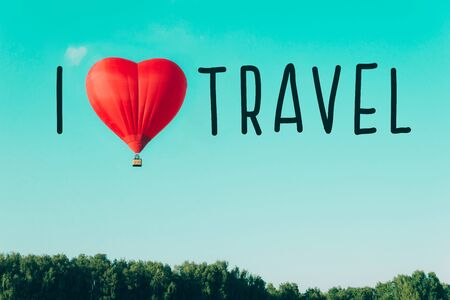 Red hot air balloon and cloud in the shape of a heart against the blue sky. Concept of love and peace. Text I love travel.