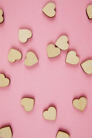 Wooden hearts on a pink background. Pattern for Valentine's Day. Symbol of love.