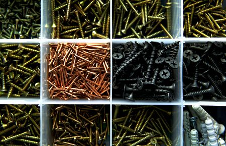 Different screws and nails in the box. Maintenance, reparing concept. Case with small construction objects. Isolated tool box.
