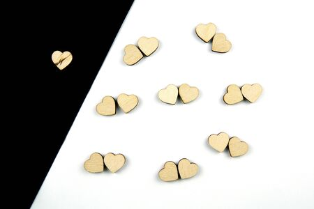 A lot of wooden hearts placed by couples on white background and one on black background. Concept of love and loneliness, isolation. Flat lay.