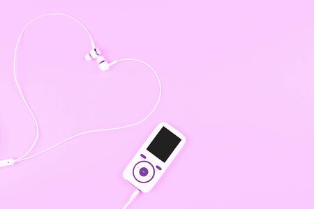 White music player with earphones laying in a shape of a heart on pastel purple background. Concept of love with music. Place for text, flat lay. 写真素材