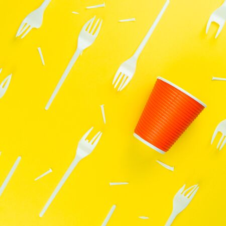 Pattern of a lot of broken plastic forks, and plastic cup on a yellow background. The concept of environmental problems, environmental pollution by plastic waste. Top view.