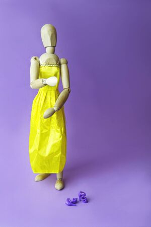 Concept of gender dysphoria and transgenders. Gestalta wearing a yellow dress, woman shoes on purple background. Place for text.