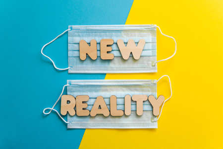 NEW REALITY words on protective face masks on blue and yellow background. Post covid-19 pandemic changes, new normal, wearing face mask in public concept. Copy space.