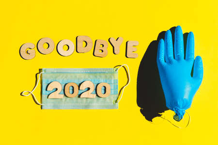 Words GOODBYE 2020 from wooden letters, inflated medical glove waving bye-bye and facemask on a yellow background. Year 2020 and epidemic concept.