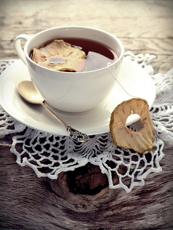 Cup of tea with dried apple on napkin photo