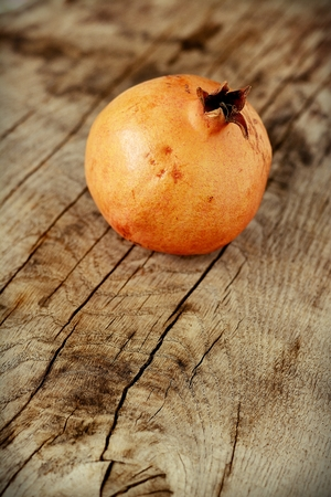 Juicy pomegranates on wooden table photo