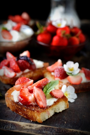 strawberries sandwiches with cream cheese and mint closeup on a rustic table