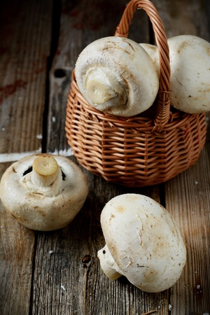 Fresh whole button mushrooms in a basket, food photo