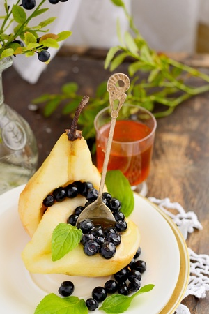 Juicy pears in bowl with fresh blueberry and honey photo