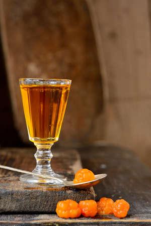 rubus chamaemorus: Bebida Cloudberry sobre fondo de madera con bayas Foto de archivo