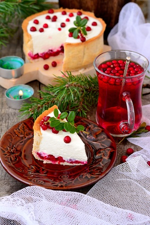 Cheese cake with cranberries on a wooden table with a glass of cranberry drink and pine branches photo