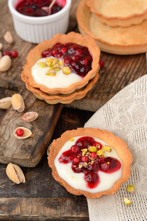 tartlets with cream berry sauce and pistachios on a wooden table with a linen napkin photo