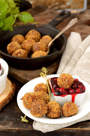 homemade meatballs with cranberry sauce on skewers on wooden table appetizer photo
