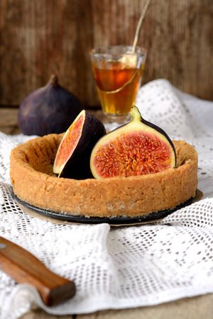 homemade tart and fresh figs on a vintage tablecloth on wooden table with honey in a glass. See series photo
