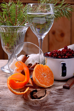 ingredients for making autumn winter spiced cranberry drink tangerines, cranberries, cinnamon and sugar on wooden table decorated with pine branches alive photo