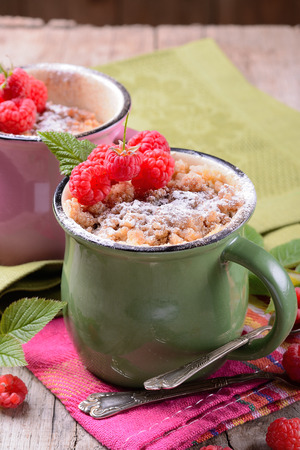 Warm chocolate cake with raspberries in a mug sprinkled icing sugar on a napkin