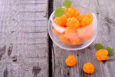organic fresh northern cloudberries in vintage glass glass on a wooden background 版權商用圖片
