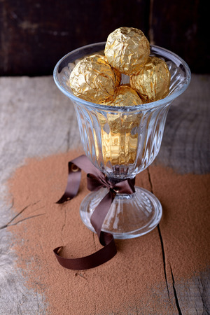 enticement: Chocolate candies assortment in glass bowl on wooden background. Selective focus