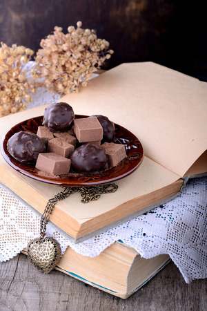 confect: Chocolate truffles on old books with vintage lace on wooden table. Chocolate bonbon assortment closeup. Selective focus Stock Photo