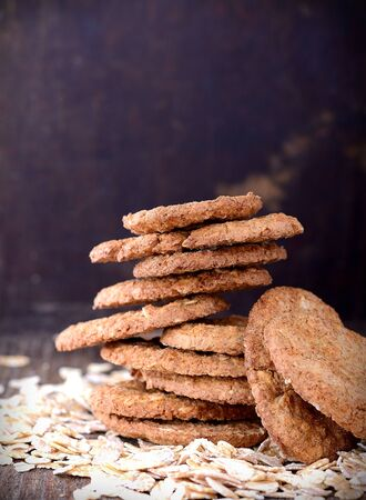 oatmeal cookies: thin oat flakes  crackers on an old wooden background. Selective focus Stock Photo