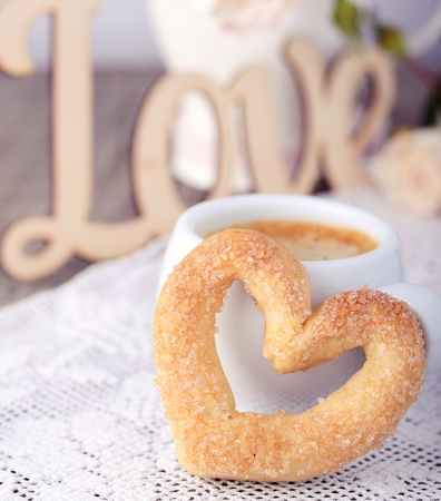 Heart-shaped biscuit on wooden background. Selective focus.  photo