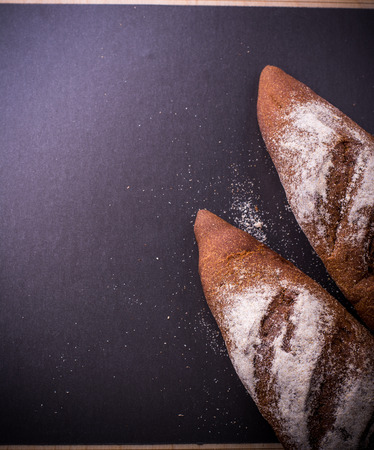 french roll: Rustic bread roll or french baguette, wheat and flour on black chalkboard. Rural kitchen or bakery - background with free text space.