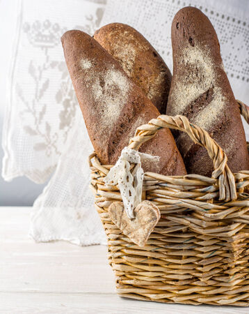 Wicker basket with different types of freshly baked bread on a white lace tablecloth photo