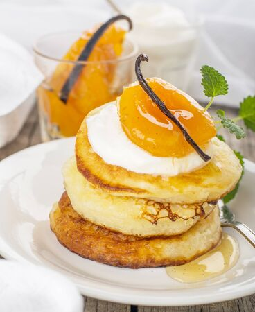 breakfast food: Pancakes with yoghurt and apricots for breakfast on wooden background with a white cloth decorated with vanilla bean