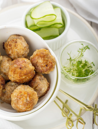 Minced meat balls with cucumber cress in a white bowl on a white background with a tablecloth  . Selective focus photo