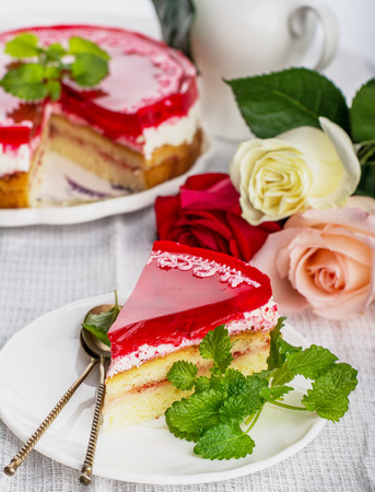 a piece of strawberry cake jelly on white background decorated with fresh roses and mint leaves. selective Focus photo