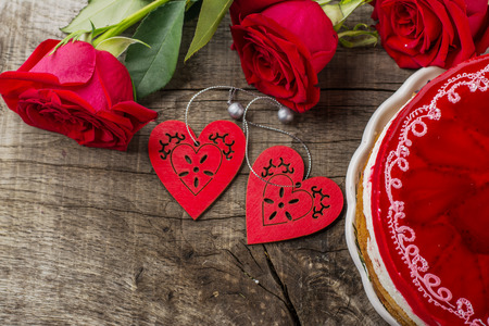 bright cake with strawberries and strawberry jelly on the wooden background with bright roses.  photo