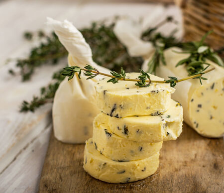 potherbs: Butter with thyme and rosemary and lemon zest. Sliced on a wooden board with herbs. selective Focus Stock Photo