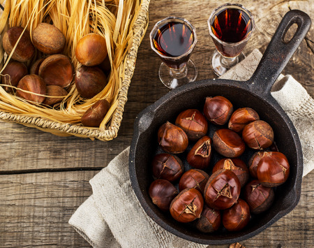 Roasted chestnuts in a cast iron skillet on a wooden fone.Vyborochny focus Standard-Bild