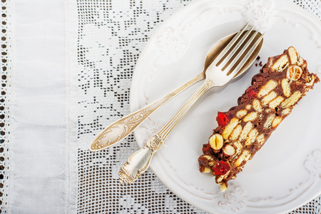 quick snack: Delicious biscuits salami with cocoa, hazelnuts and cherries on a white plate with silver fork and spoon. Against the background of white lace vintage tablecloths