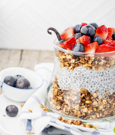 Strawberry, blueberries, oatmeal and chia seeds pudding in a jar for breakfast Stock Photo