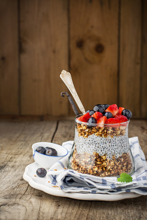 Chia Seed Pudding and caramel oat flakes, blueberries and strawberries in a transparent glass on a wooden background. Selective focus. Concept of healthy food Standard-Bild