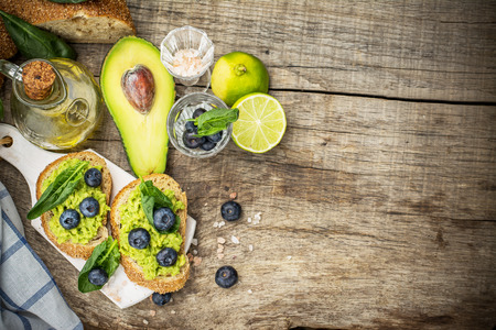 Sandwiches with avocado, blueberries and spinach on a dark grain bread. Selective focus. The concept of nutrition.